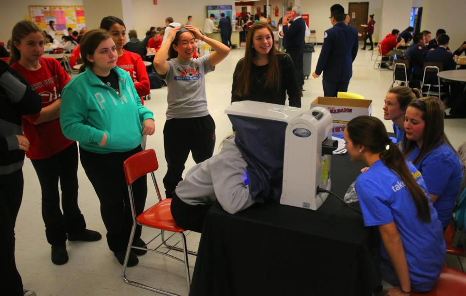 Students at North Quincy High School queue up to peer into a skin analyzerbrought in by  the Melanoma Foundation of New England.