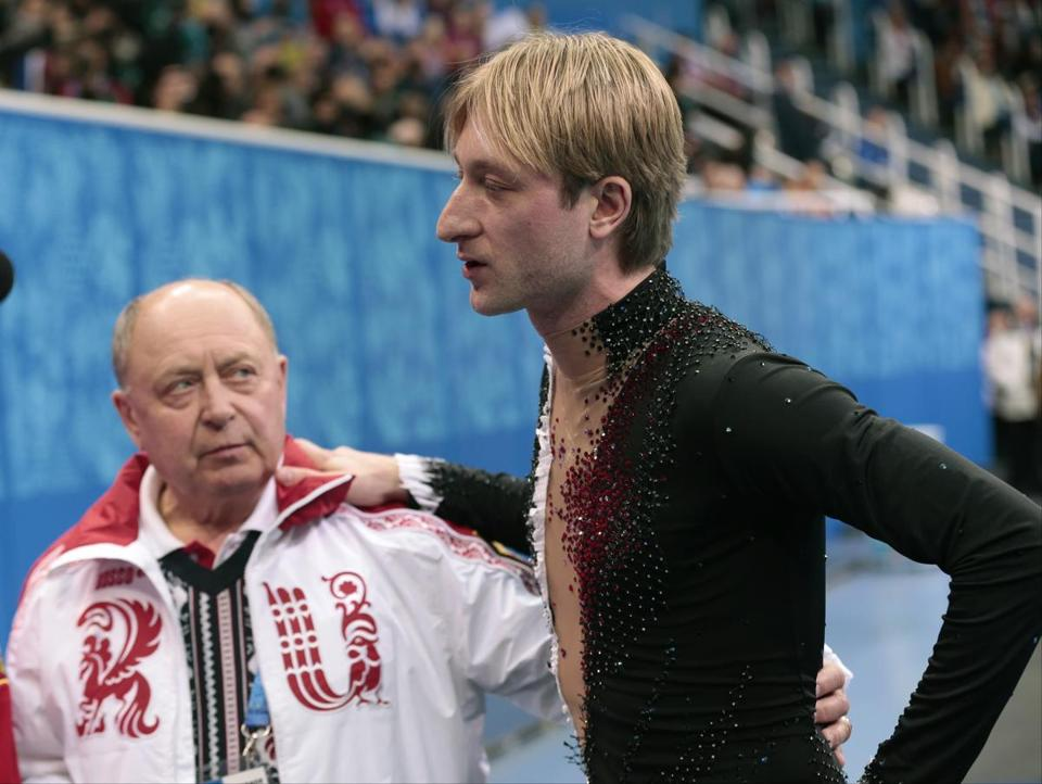 Evgeni Plushenko, with coach Alexei Mishin, left the ice after withdrawing from competition.