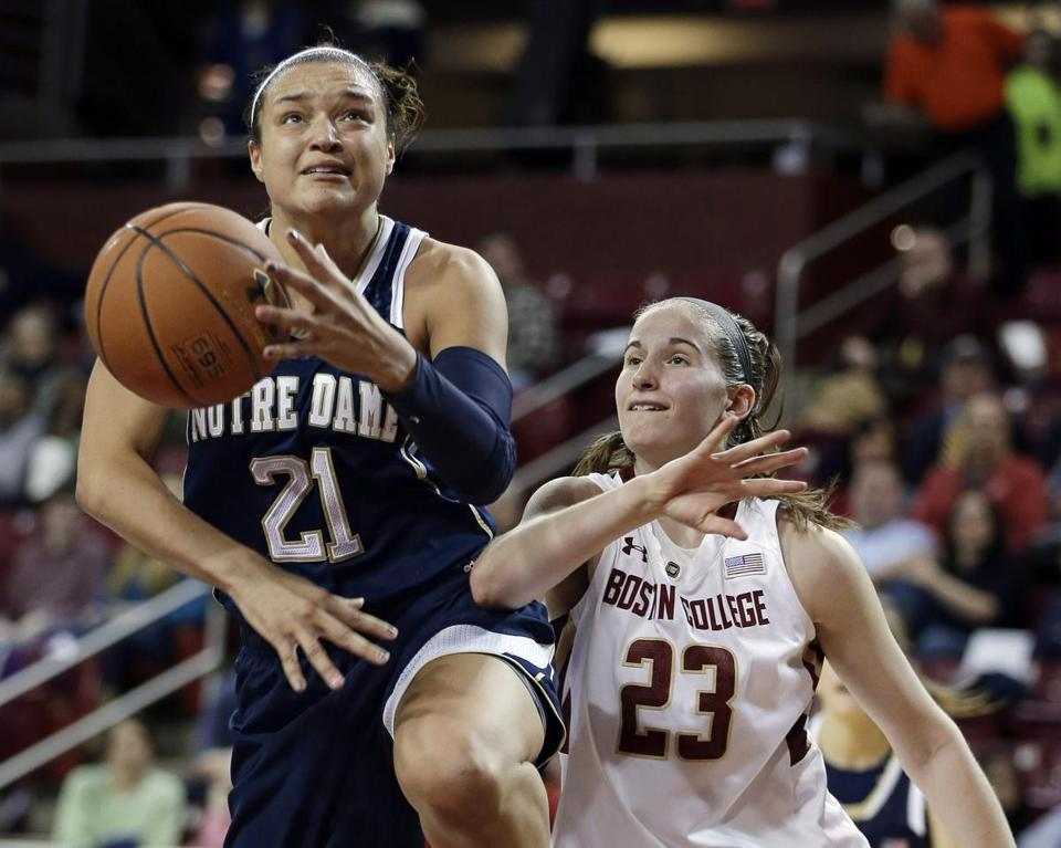 BC guard Kelly Hughes can't keep up with Notre Dame's Kayla McBride, fouling her during a shot attempt.