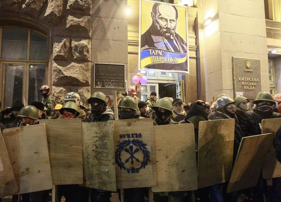 Antigovernment protesters carried makeshift shields and covered their faces as they left City Hall in Kiev on Sunday.
