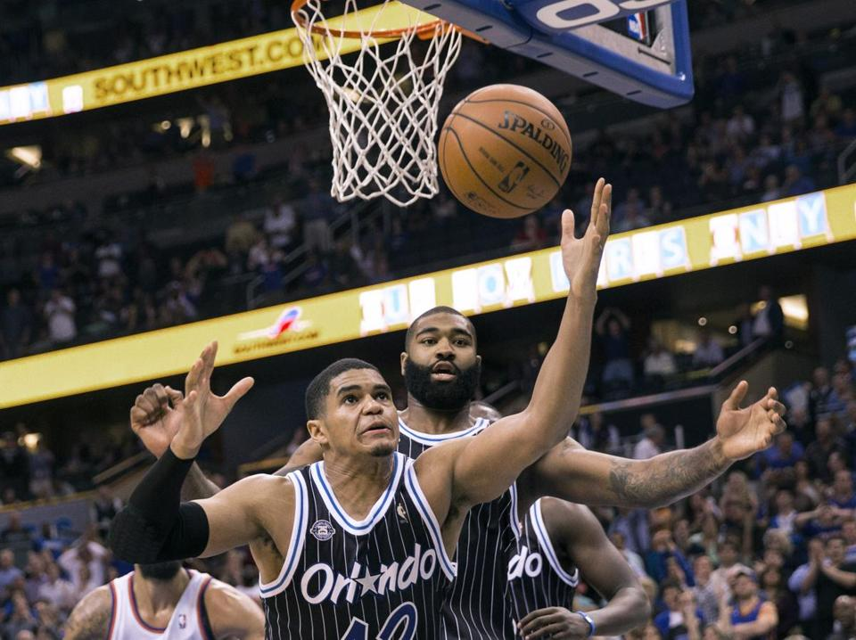 Orlando's Tobias Harris (12) and Kyle O'Quinn (right) reached for a rebound after a missed shot.