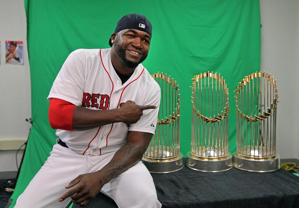 Sox slugger David Ortiz points at the 2004, 2007, and 2013 World Series trophies, which he had a big hand in.