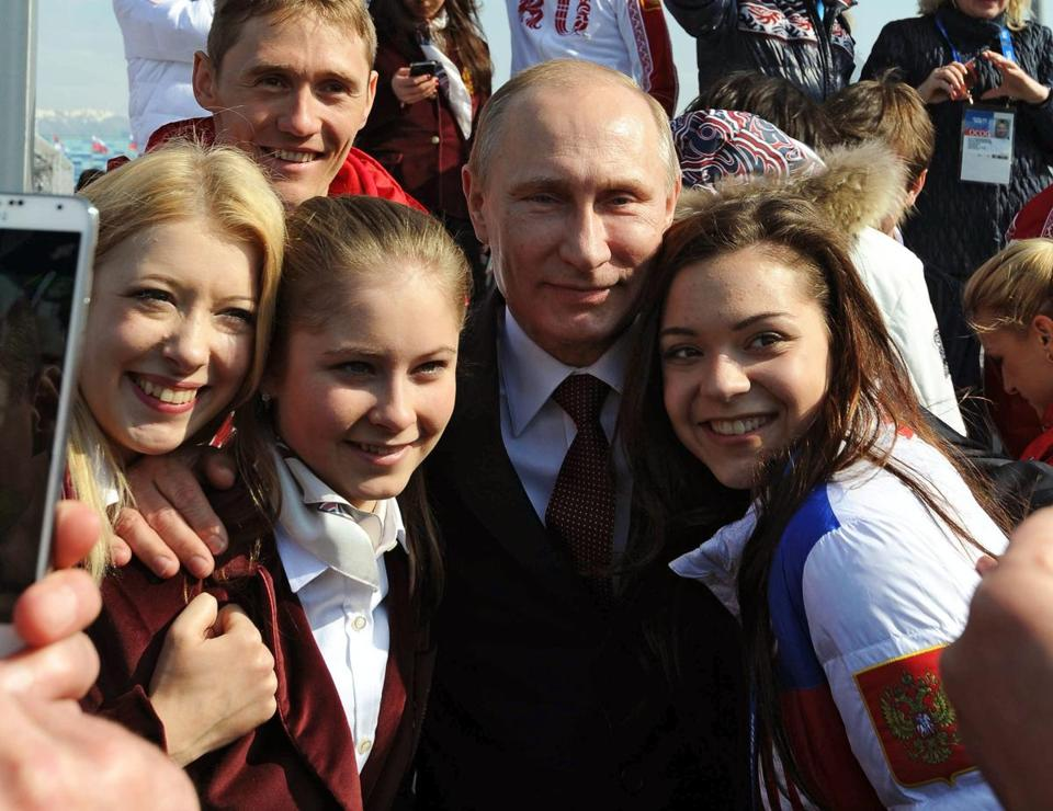 Russian President Vladimir Putin posed with figure skaters and cross country skier during celebrations of the Russian team victory in the Sochi 2014 Olympic Games.