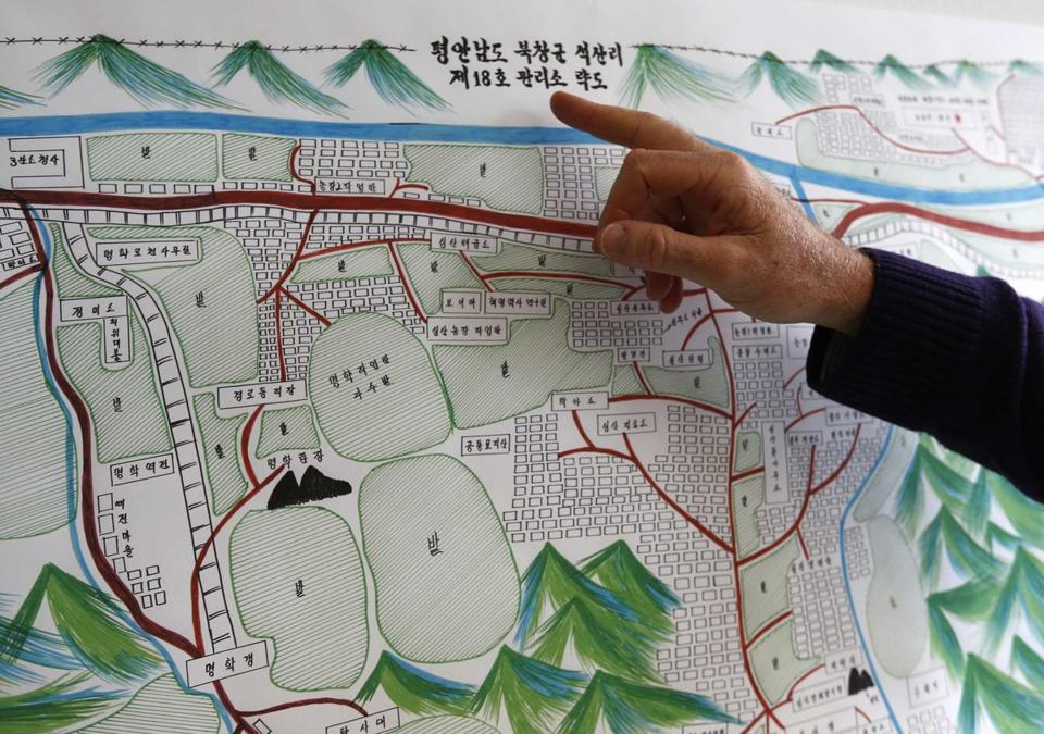 A UN staff member points to the title of a drawing of North Korean labor camp No. 18. The drawing was made in 2012 by survivor Kim Hye Sook.