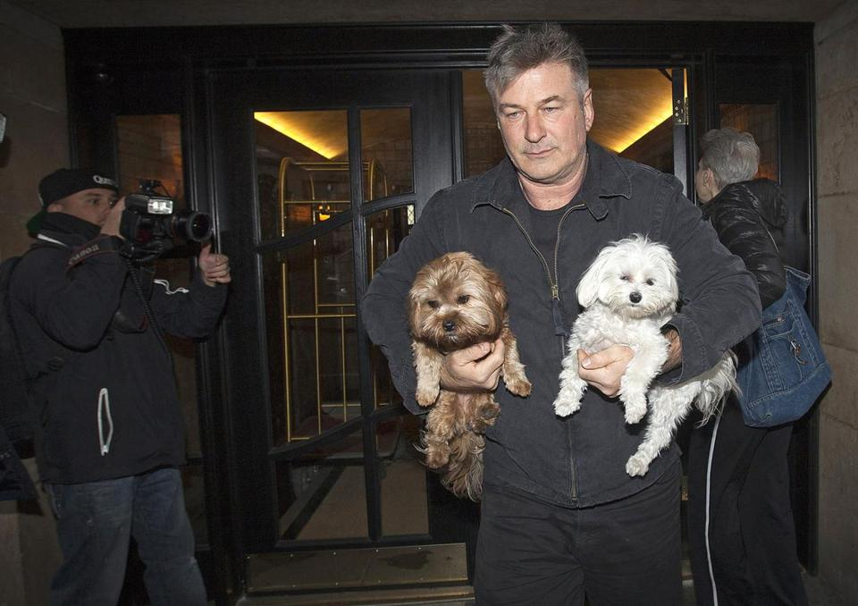 Alec Baldwin walked out of his New York apartment building carrying two dogs in New York last year.