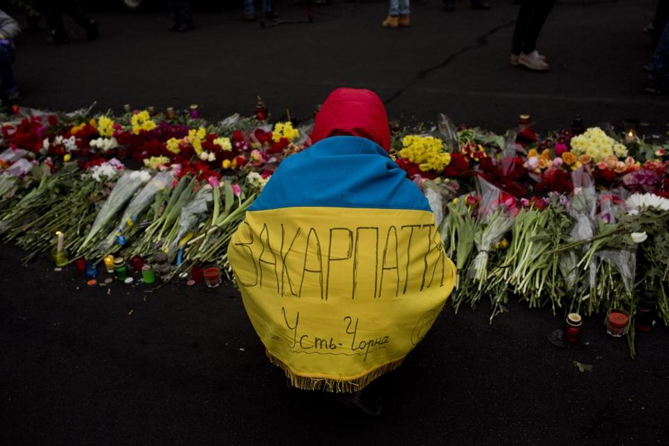 An anti-Yanukovych protester, wrapped in a Ukrainian flag with the name of his village on it, placed flowers Tuesday at a memorial for those killed in clashes with police in Kiev.