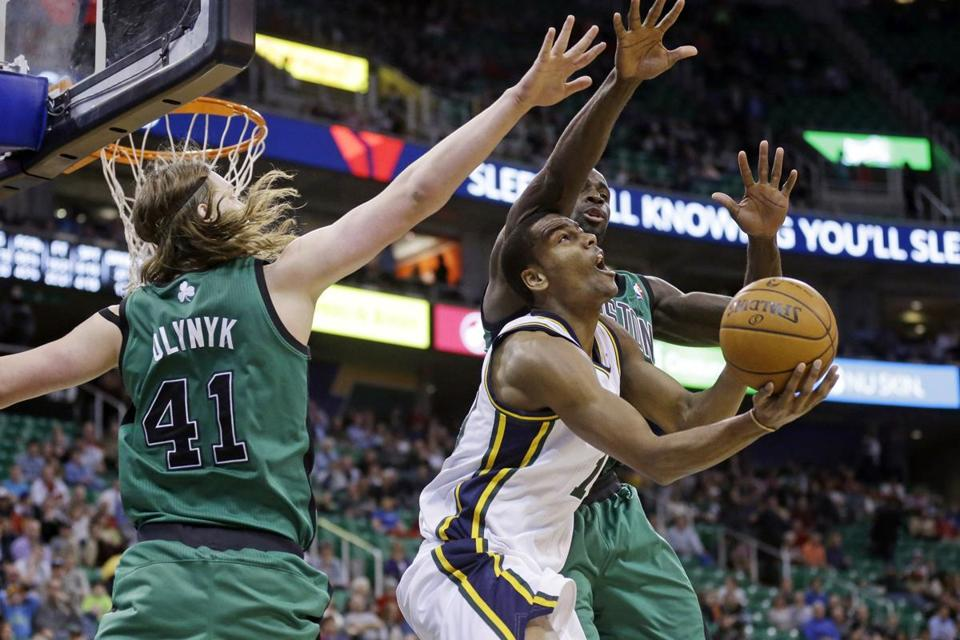 Utah's Alec Burks (team-high 21 points) was in the middle of the Jazz's victory, as well as between Celtics forwards Kelly Olynyk and Brandon Bass.