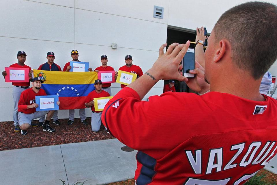 Christian Vazquez clicks away as Red Sox from Venezuela pose with their country's flag and messages calling for peace.
