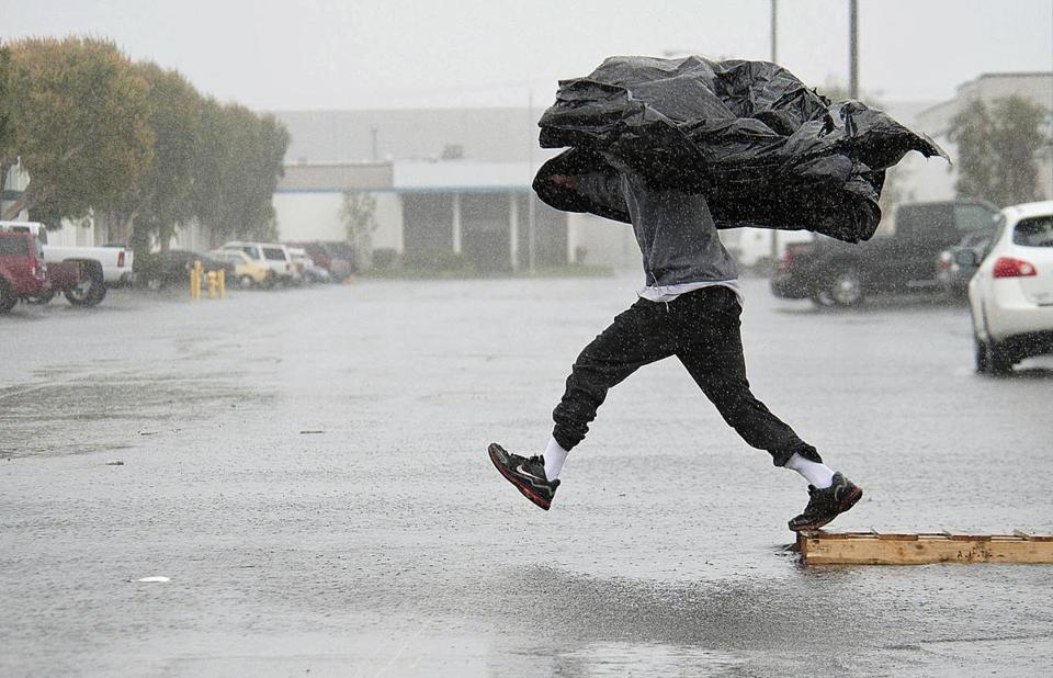 Assembly worker Terry Young of Rialto, Calif., navigated a flooded parking lot via a wooden pallet to get to a food truck during his break Friday in Anaheim amid a powerful Pacific storm.