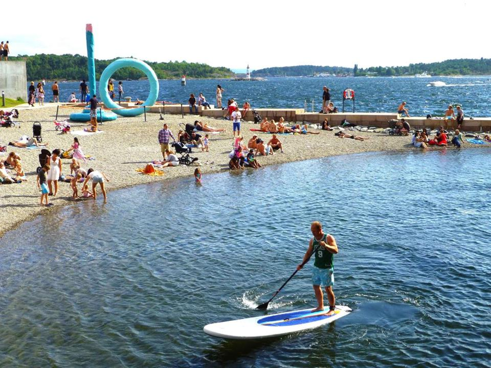 People of Oslo gravitate to the beach at Tjuvholmen on the Oslo fjord.