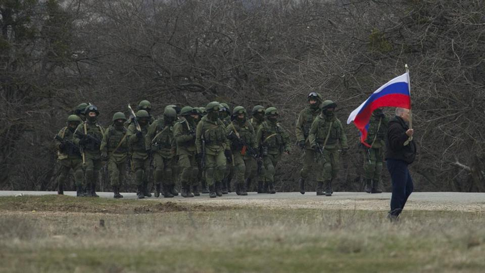 Russian soldiers walked as a local resident waved a Russian flag outside of a Ukrainian military base in the Crimean village of Perevalne.