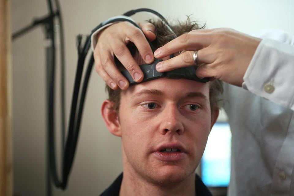 Tufts University student Sam Hincks is fitted with a headband that transmits light through the forehead and reads brain activity.