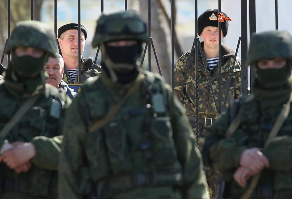 Ukrainian soldiers stood inside the gate of a Ukrainian military base as unidentified heavily-armed soldiers stood outside the gates.