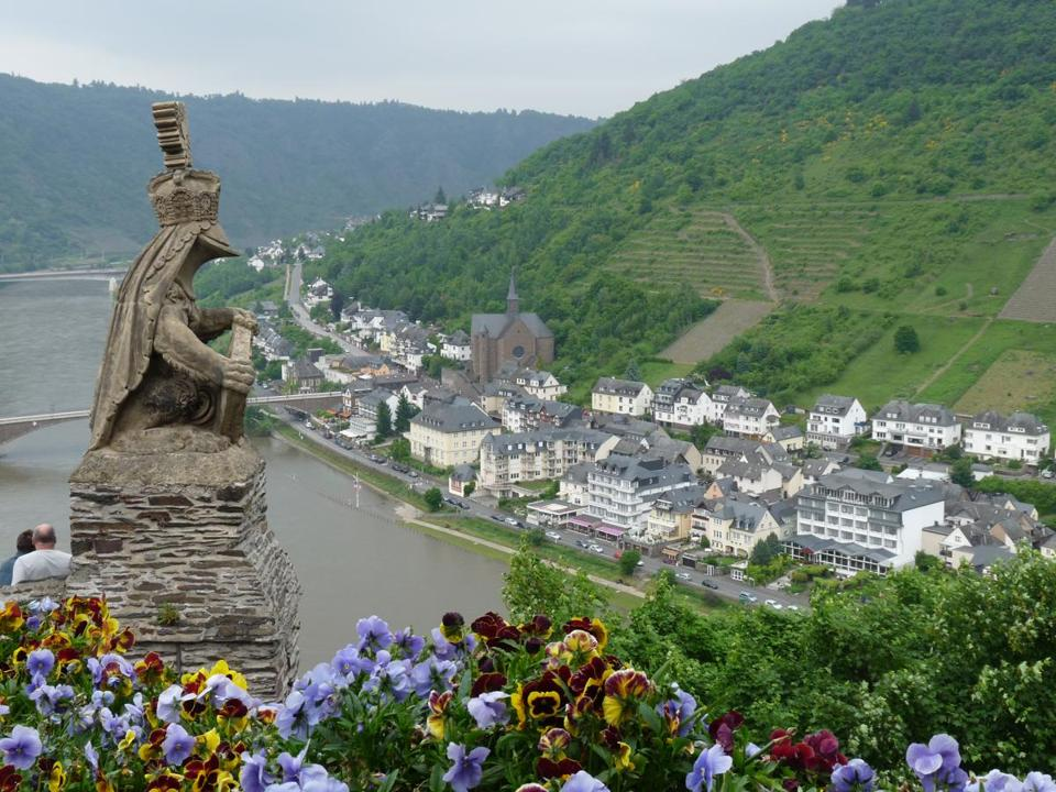 A gargoyle on the castle in Cochem, Germany, has a vantage point over the Moselle Valley, its steep vineyards, and the riverside town.