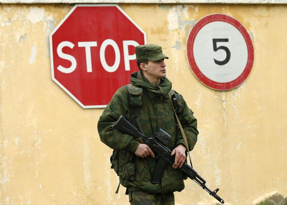 A uniformed man, believed to be a Russian serviceman, stood guard near a Ukrainian military base outside the Crimean city of Sevastopol.