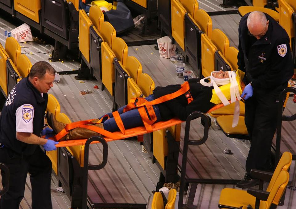 A woman was removed from TD Garden on a stretcher after a net hanging above one of the goals fell onto her following the game.