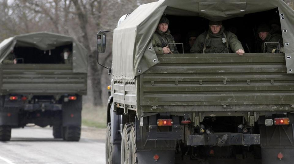A Ukrainian official said Russia was moving a convoy of unmarked military vehicles on Saturday toward an airfield near Crimea's regional capital.