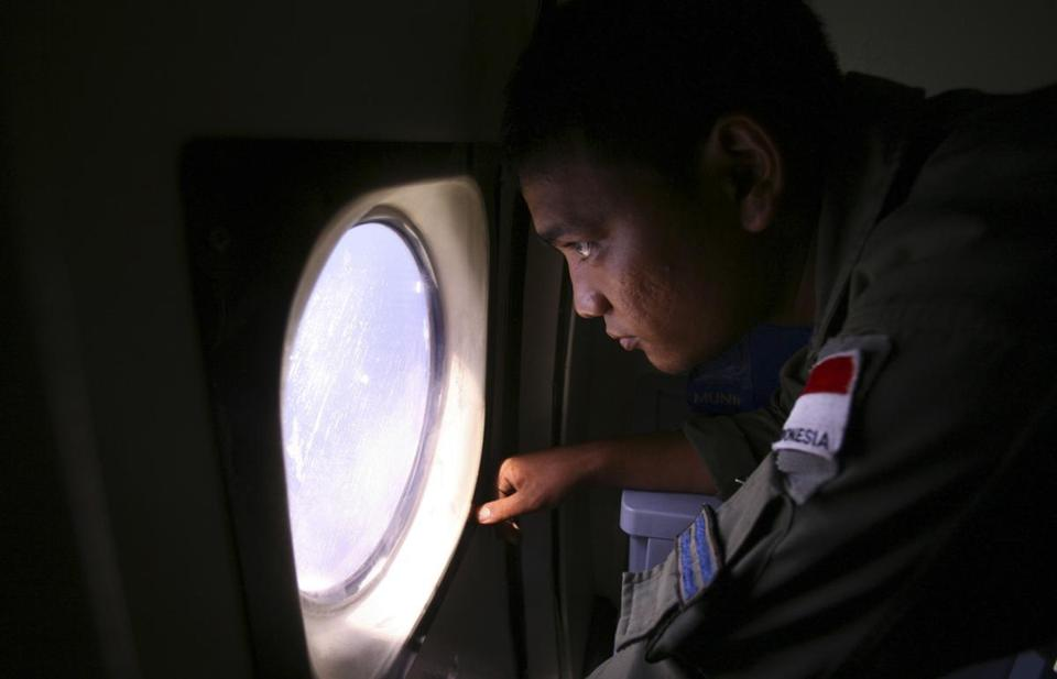 An Indonesian Navy crew member scanned the ocean. About 40 ships and 34 aircraft have joined the search efforts.