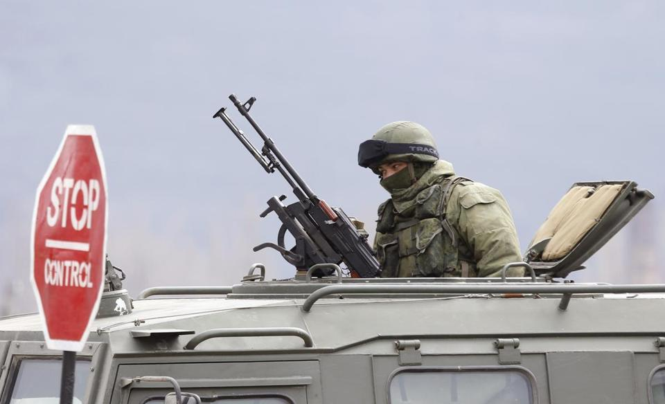 An armed man, believed to be Russian serviceman, sits in an armored military vehicle in a village outside Simferopol Tuesday.