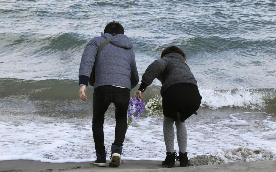 Employees of a nursing home tossed flowers into the sea in remembrance of the 36 people who died in the home.
