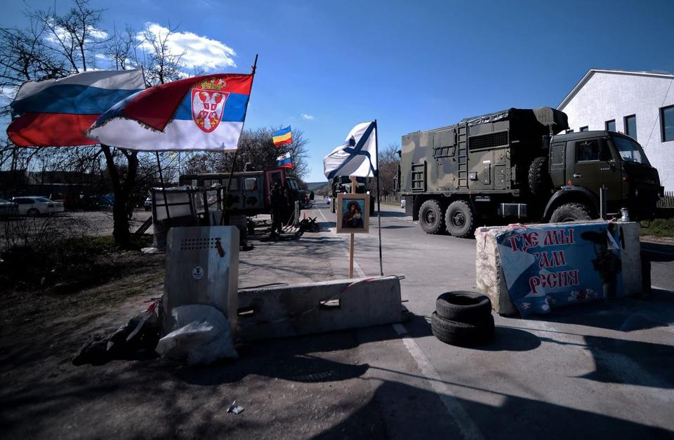 A Russian flag (L) floats alongside a Serbian flag (2nd L) and a Russian navy flag (C) as a military truck belonging to Russian forces passed a check point on the road from Simferopol to Sevastopol.