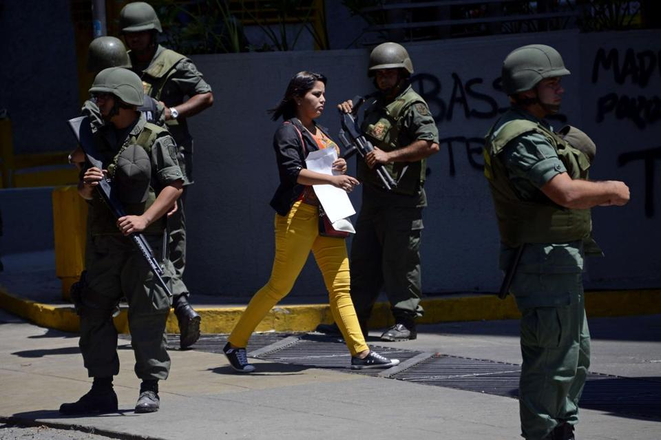 A woman walked amid members of the National Guard deployed at opposition stronghold Altamira square.