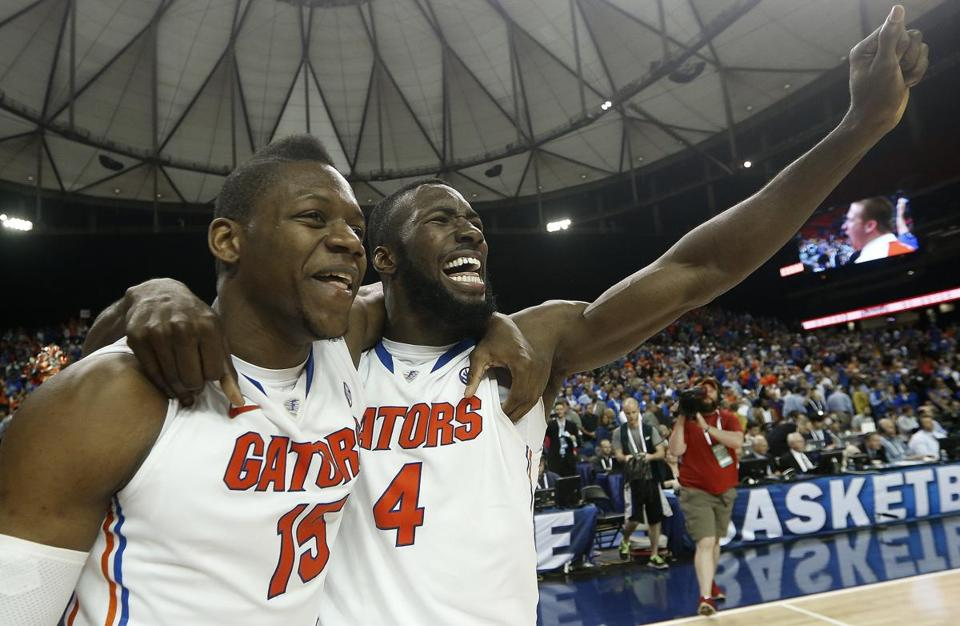Florida's forward Will Yeguete (15) Patric Young (4) celebrate after the second half of an NCAA college basketball game against Kentucky in the Championship round of the Southeastern Conference men's tournament, Sunday, March 16, 2014, in Atlanta. Florida won 61-60. (AP Photo/John Bazemore)