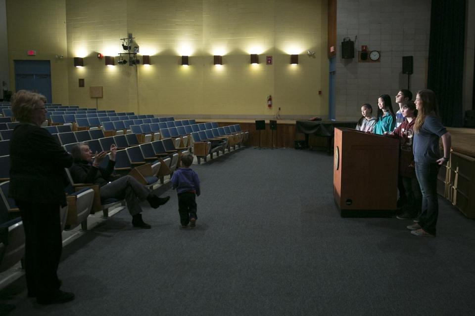 Lincoln officials Susan Brooks and Sarah Cannon Holden (seated near her grandson) talk with students about Town Meeting.