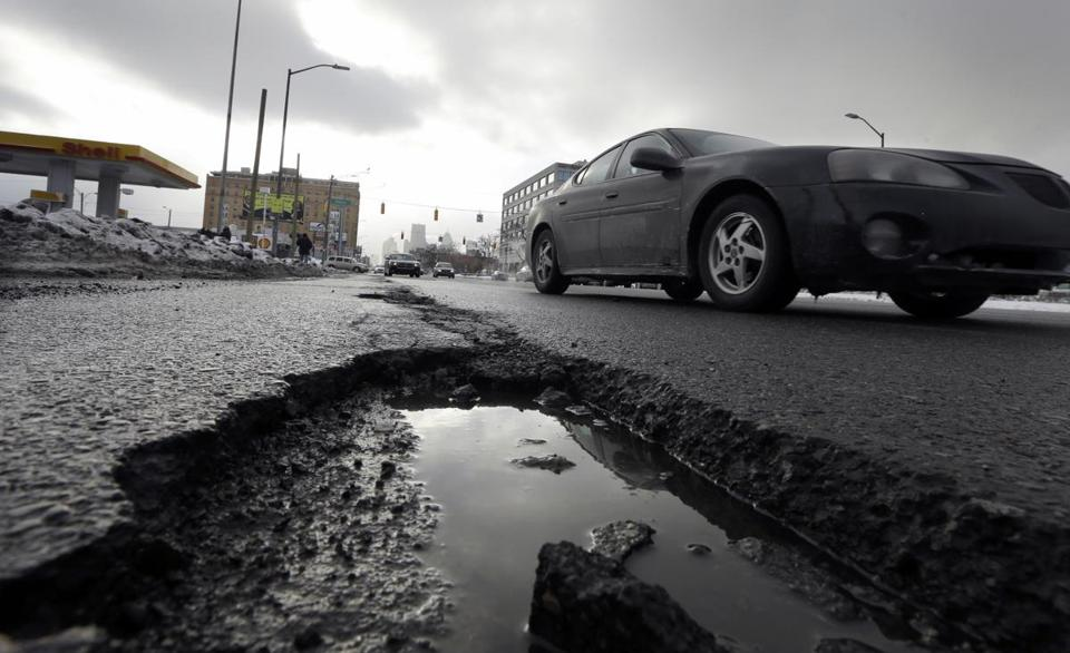 A car drives by a pothole in Detroit last month. Attorneys for Detroit's two pension funds are seeking approval for a plan that would cut pensions and other benefits.