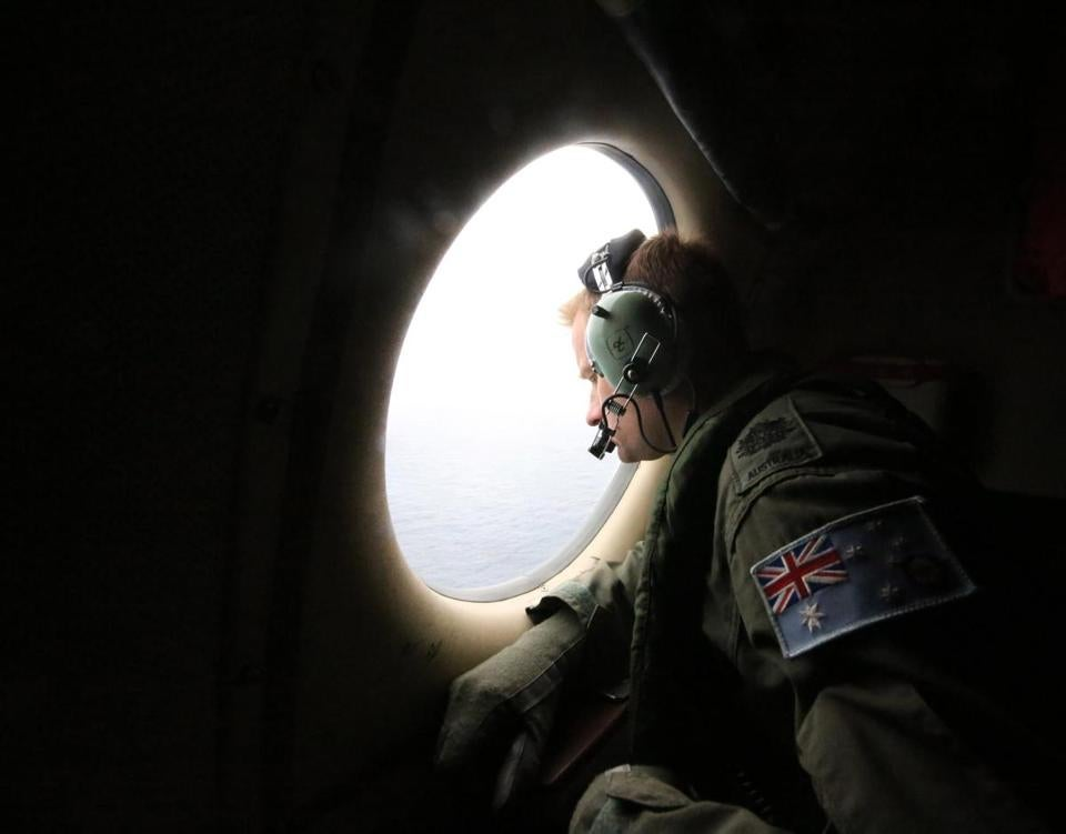 A crew member on a Royal Australian Air Force P-3 Orion aircraft scanned the ocean  for signs of debris.