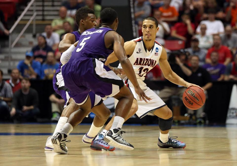 Arizona's Nick Johnson is closely guarded by Jordan Richardson of Weber State. (Photo by Jeff Gross/Getty Images)