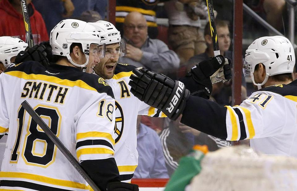 Boston Bruins' Patrice Bergeron, second from left, celebrates his goal against the Phoenix Coyotes with teammates Reilly Smith (18) and Andrej Meszaros (41), of the Czech Republic, during the first period of an NHL hockey game on Saturday, March 22, 2014, in Glendale, Ariz. (AP Photo/Ross D. Franklin)