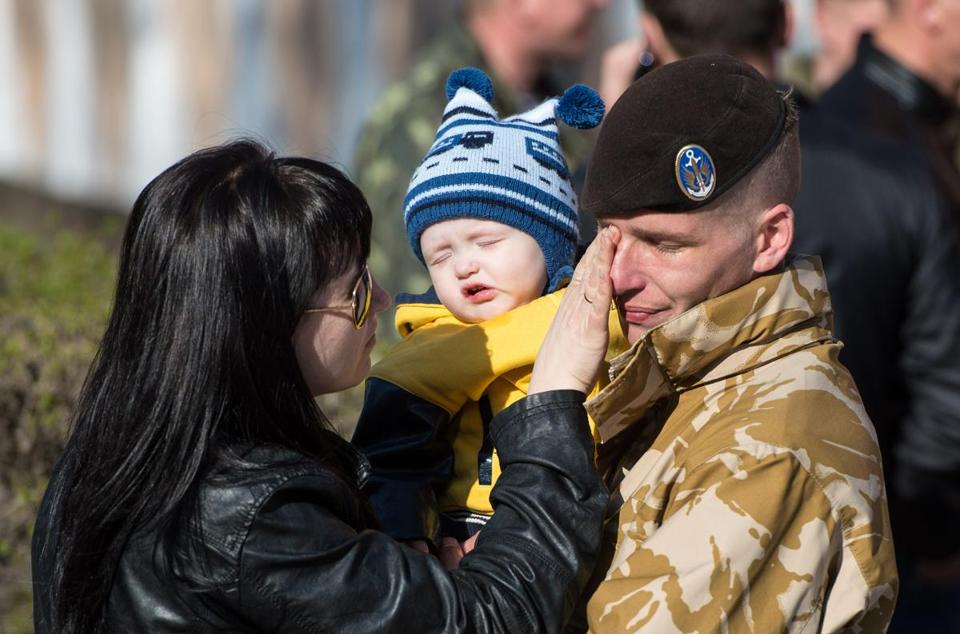 A Ukrainian marine shared a tender moment with his family as Ukraine's only marine battalion left its garrison in the eastern Crimea's port city of Feodosiya on Monday.