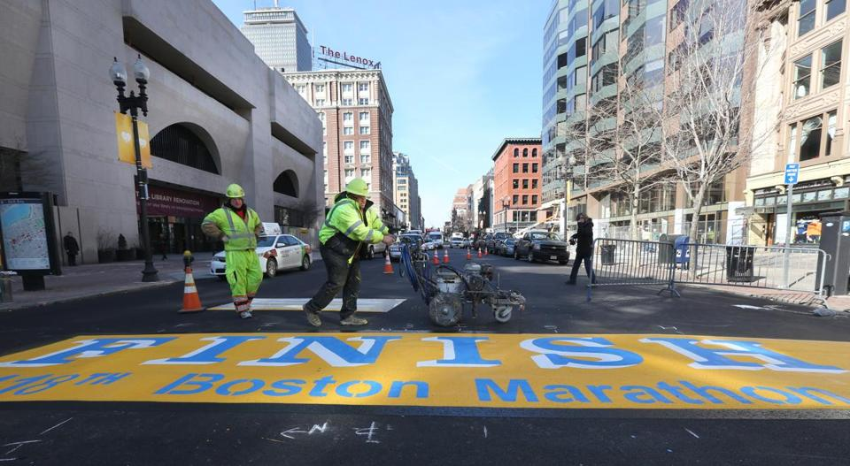 James Sawler (left) and Eric House of Road Safe Traffic Systems put some final touches on the Boston Marathon finish line.