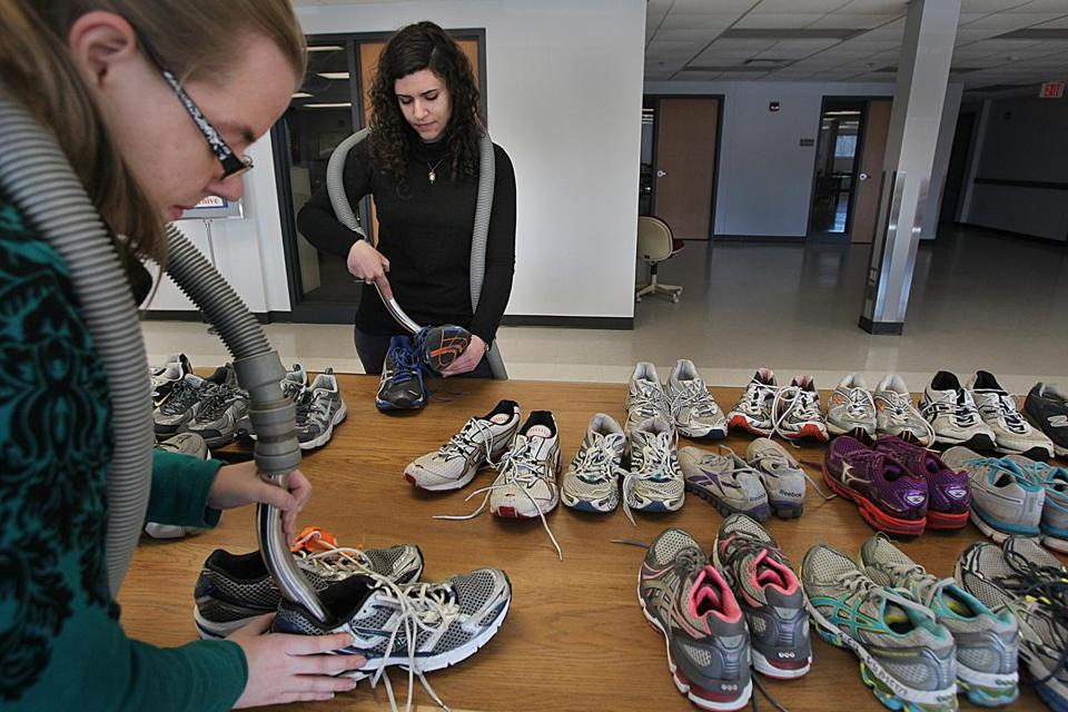 Tiffany Locke (left) and Emily Shafer prepared shoes for the exhibit, which will open on April 7.