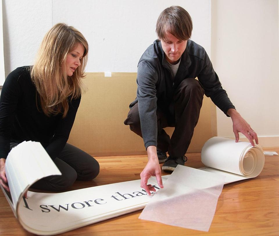 Artists Kelly Sherman (left) and Halsey Burgund unroll panels that are part of their audio-visual-Internet project on patient interactions with the often-impersonal health care system.