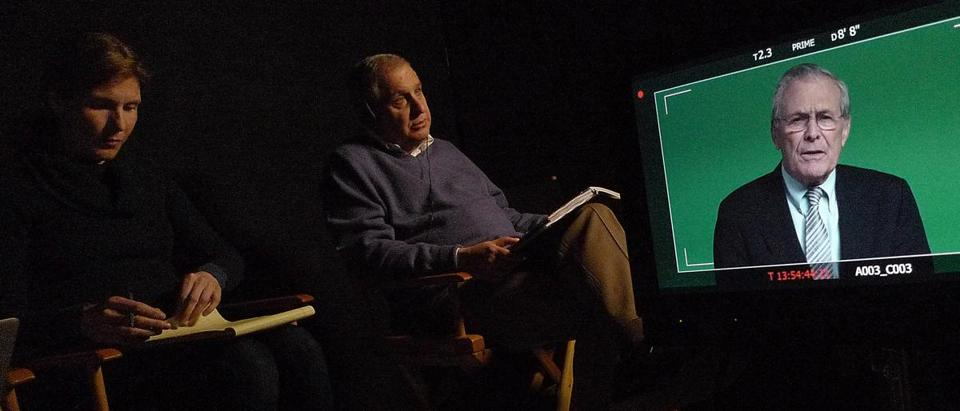 "Errol Morris watches Donald Rumsfeld, subject of ""The Known Unknown,"" on screen."