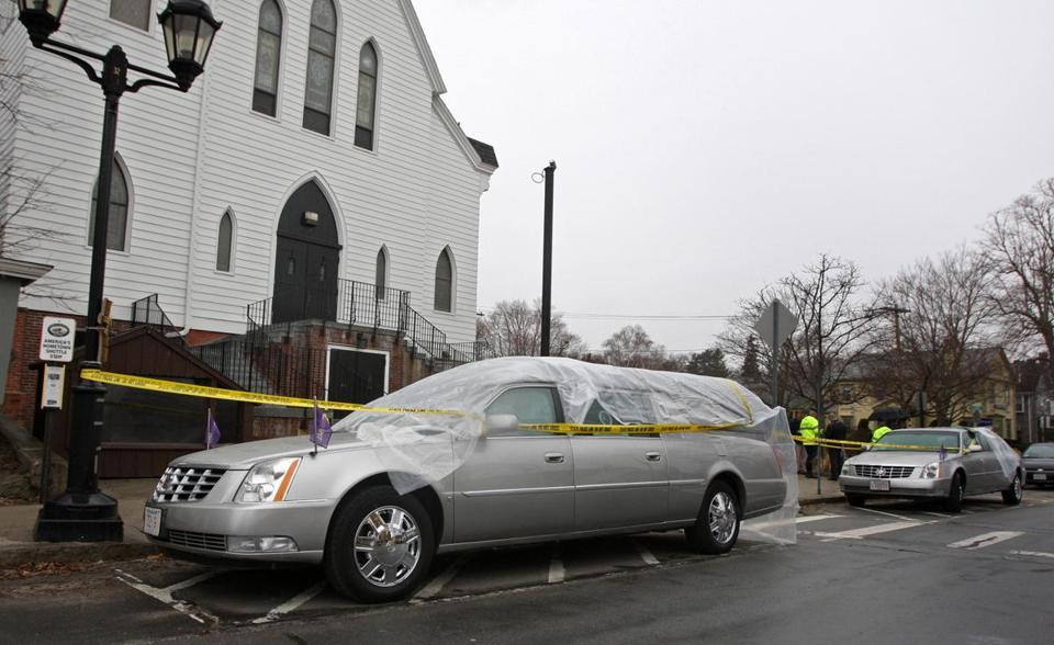A hearse and limousine were covered in plastic and police tape in front of the Church of St. Peter in Plymouth.