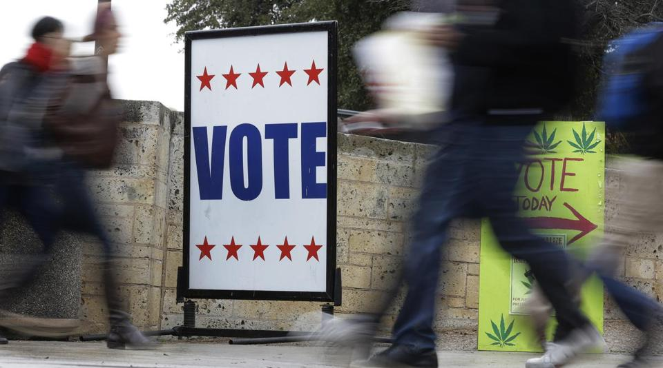 Pedestrians passed voting signs near an early-voting polling site in Austin, Texas, last month. In elections beginning next week, voters in 10 states must show photo IDs.