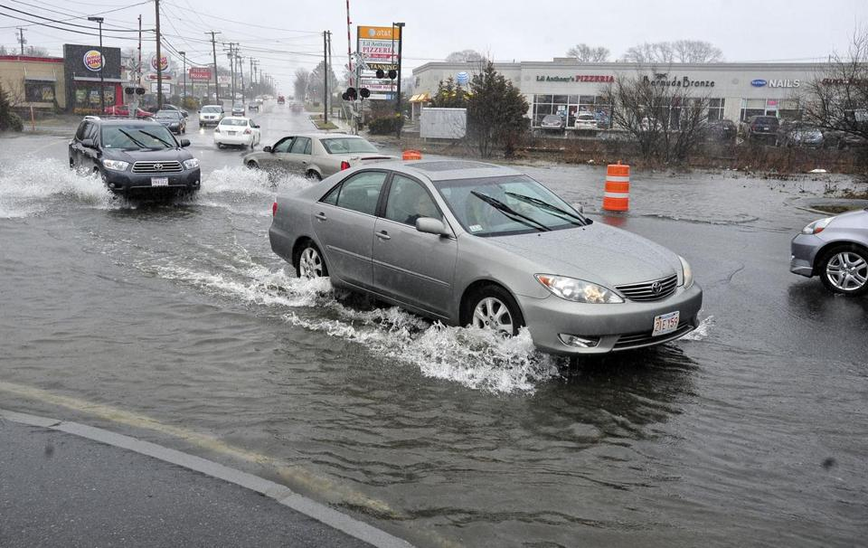 Drivers navigated a flooded street in New Bedford.