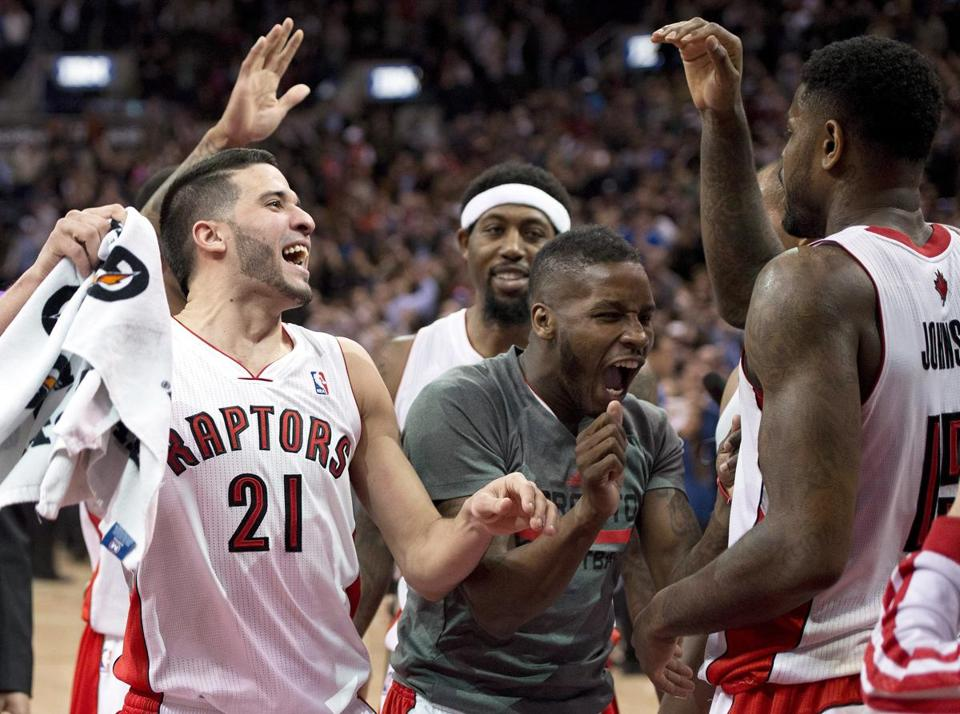 Toronto's Amir Johnson (right), who made the game winning shot Friday, was congratulated by teammates Greivis Vasquez (left) and Dwight Buycks after knocking off the Celtics.