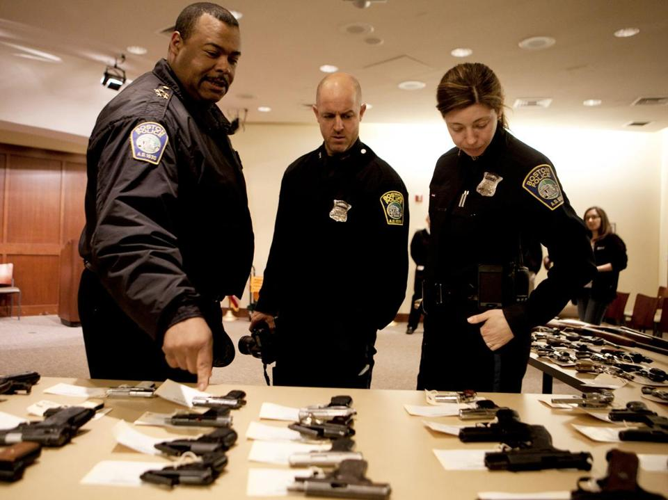Boston Police Chief William Gross, officer James Kenneally, and officer Rachel McGuire examined guns from the buyback.