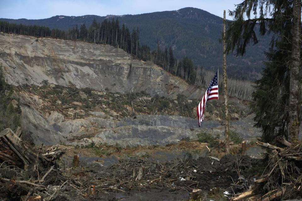 An American flag hangs from the only cedar post left standing at the scene of a deadly mudslide.