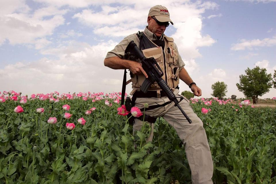 An American security contractor walked through an opium poppy field near Lashkar Gah in Helmand province of southern Afghanistan.