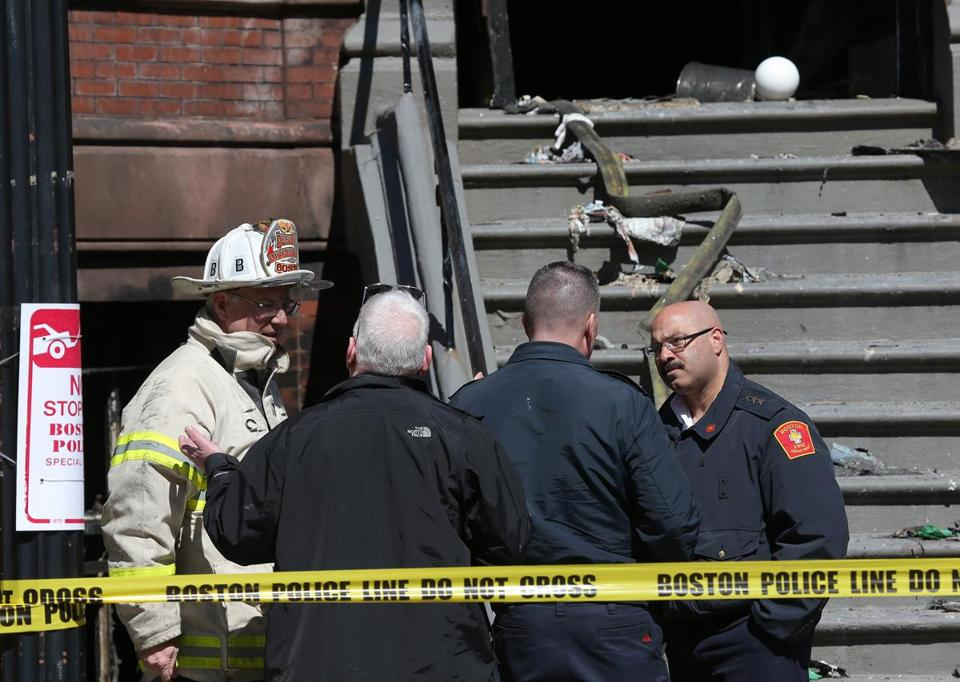 Members of the Boston Fire and Police departments talked in front of the building where a blaze killed two firefighters last week.