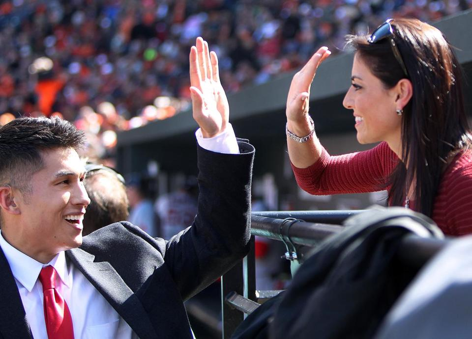 Former NESN sideline reporter Jenny Dell high fives NESN's Gary Striewski at Orioles Park at Camden Yards.