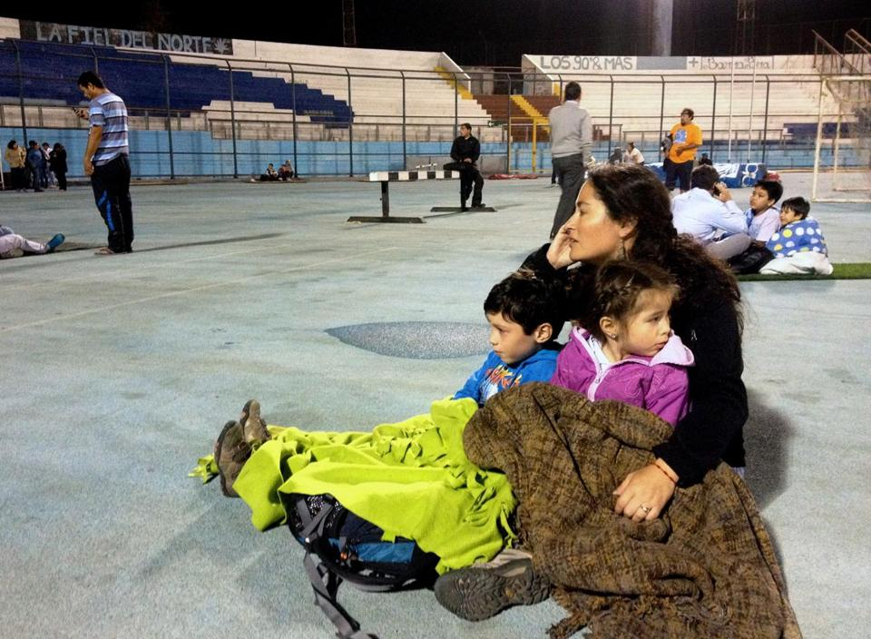 Residents in Iquique, Chile, took refuge at the city stadium following a tsunami alert after an 8.2-magnitude earthquake hit off Chile's Pacific coast.