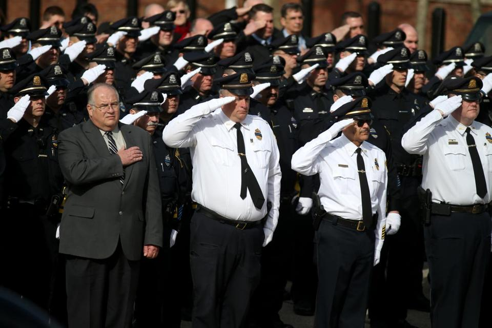 The hearse carrying Plymouth Police Officer Gregg Maloney receives a salute from fellow officers at the Plymouth Police Headquarters.