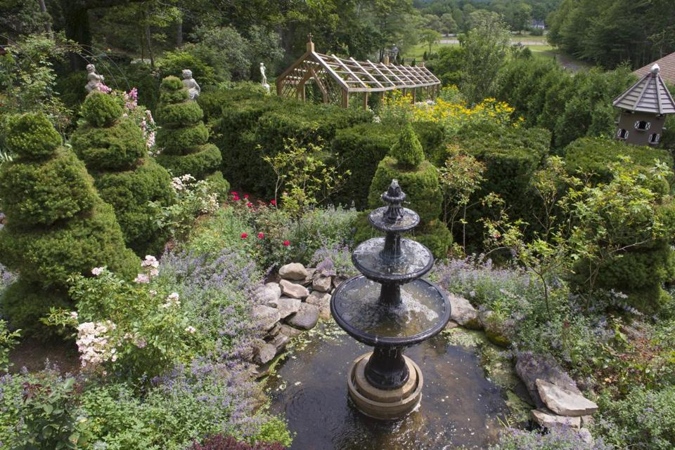 A tiered birdbath and raised dovecote at the top of the garden overlook a riding arena.
