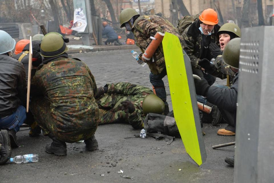 Protesters reacted to sniper gunfire in Kiev's Independence Square on Feb. 20. The identity of the snipers believed to be responsible is the subject of disagreement.